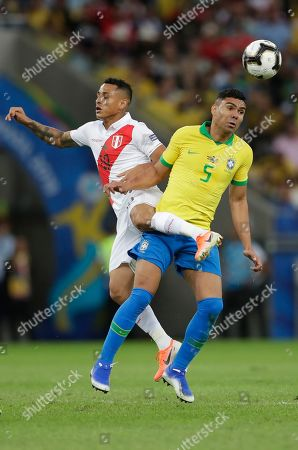 Peru's Yoshimar Yotun, left, goes for a header with Brazil's Casemiro during the final match of the Copa America at Maracana stadium in Rio de Janeiro, Brazil