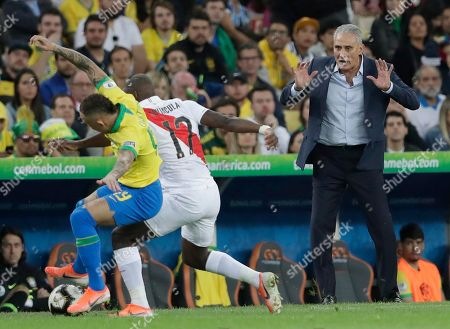 Brazil's coach Tite, right. gives instructions to his players as Brazil's Everton, left, and Peru's Luis Advincula, center, fight for the ball during the final match of the Copa America at Maracana stadium in Rio de Janeiro, Brazil
