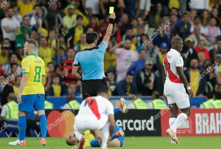 Referee Roberto Tovar awards a yellow card to Peru's Luis Advincula, right, during the final match of the Copa America against Brazil at Maracana stadium in Rio de Janeiro, Brazil