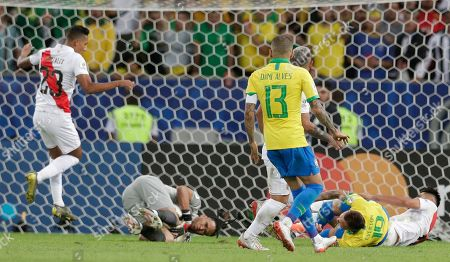 Peru's goalkeeper Pedro Gallese catches the ball as Brazil's Everton, right, is fouled in the penalty area by Peru's Carlos Zambrano during the final match of the Copa America at Maracana stadium in Rio de Janeiro, Brazil