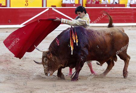 Stock Photo of Spanish bullfighter Alberto Lopez Simon performs a pass on a bull during the bullfight of Pamplona's Bull Fair, in Pamplona, Navarra, Spain, 07 July 2019.