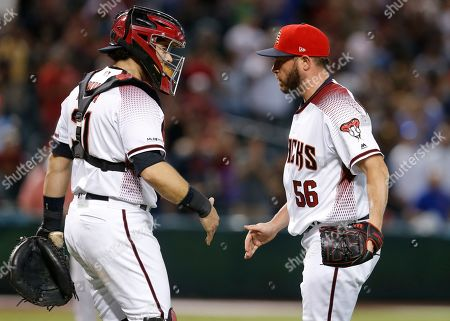 Arizona Diamondbacks pitcher Greg Holland, right, and Alex Avila, left, celebrate after defeating the Colorado Rockies 5-3 during a baseball game, in Phoenix