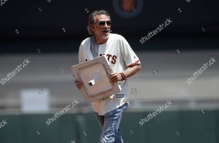 Musician Kenny Loggins carries a base off the field between innings of a baseball game between the San Francisco Giants and the St. Louis Cardinals in San Francisco