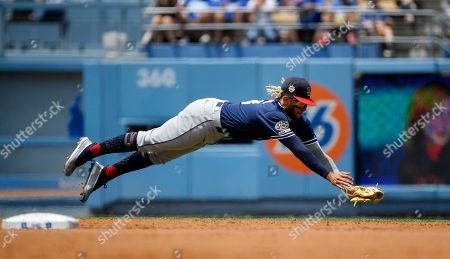 San Diego Padres shortstop Fernando Tatis Jr. makes a catch on a ground ball hit by Los Angeles Dodgers' Austin Barnes during the second inning of a baseball game, in Los Angeles. Barnes was thrown out at first on the play
