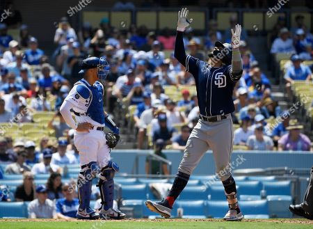 Fernando Tatis, Austin Barnes. San Diego Padres' Fernando Tatis Jr., right, gestures as he scores after hitting a three-run home run as Los Angeles Dodgers catcher Austin Barnes stands at the plate during the fifth inning of a baseball game, in Los Angeles