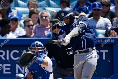 Fernando Tatis, Austin Barnes. San Diego Padres' Fernando Tatis Jr., right, hits a three-run home run as Los Angeles Dodgers catcher Austin Barnes watches during the fifth inning of a baseball game, in Los Angeles
