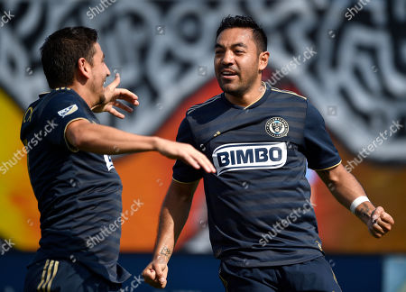 Philadelphia Union's Marco Fabian, right, celebrates with Alejandro Bedoya after scoring a goal past Orlando City goalkeeper Brian Rowe during the first half of an MLS soccer match, in Chester, Pa