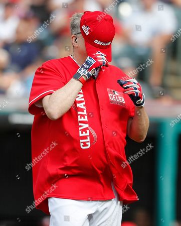 Actor Drew Carey covers his face with his cap after batting  during All-Star Celebrity Softball  Game at Progressive Field in Cleveland, Ohio, USA, 07 July 2019.