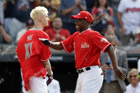 Stock Photo of Kenny Lofton, right, celebrates with Machine Gun Kelly after hitting a home run during the All-Star MLB Celebrity Softball Game, in Cleveland. The MLB baseball All-Star Game is to be played Tuesday
