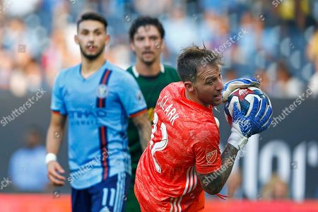 Portland Timbers goalkeeper Steve Clark, right, makes a save during the first half of an MLS soccer match against New York City, in New York