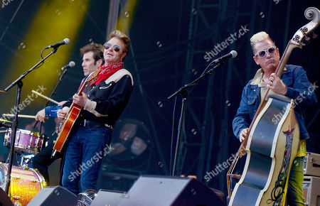 Stock Photo of Drummer Slim Jim Phantom (L), guitarrist Brian Setzer (L) and bassist Lee Rocker (R) of the US rockabilly band 'Stray Cats' perform during the 31st Eurockeennes Festival in Belfort, France, late 07 July 2019 (issued 08 July 2019). The music festival ran from 04 to 07 July 2019.