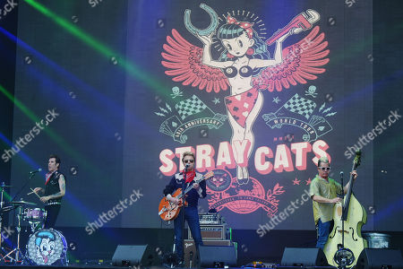 Stock Image of Drummer Slim Jim Phantom (L), guitarrist Brian Setzer (L) and bassist Lee Rocker (R) of the US rockabilly band 'Stray Cats' perform during the 31st Eurockeennes Festival in Belfort, France, late 07 July 2019 (issued 08 July 2019). The music festival ran from 04 to 07 July 2019.