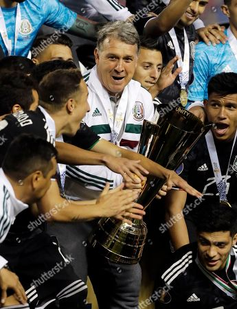 Mexico head coach Gerardo Martino, center, celebrates with his team after Mexico defeated United States 1-0 during the CONCACAF Gold Cup final soccer match in Chicago