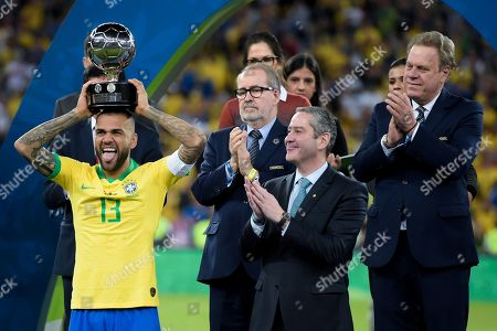 Daniel Alves of Brazil celebrates with the 'Player of the Tournament' trophy following the match