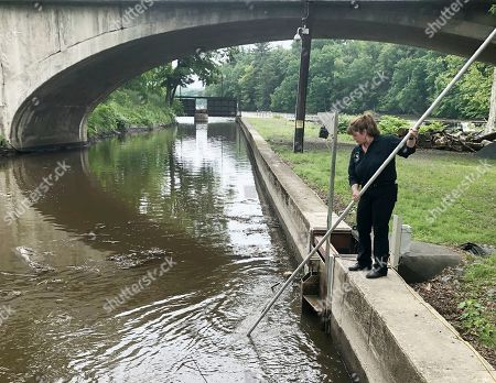 Natural Power Group co-owner Sarah Bower-Terbush cleans debris from the canal that feeds the company's hydroelectric site in Wappingers Falls, N.Y. She and her husband sell renewable power to local customers from three hydroelectric sites they operate in the Hudson Valley. Customers say they like investing their money locally in clean power