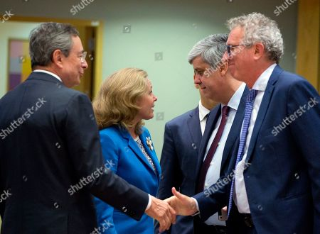 Spanish Economy Minister Nadia Calvino, second left, speaks with President of the eurogroup Mario Centeno, second right, as European Central Bank President Mario Draghi, left, shakes hands with Luxembourg's Finance Minister Pierre Gramegna during a meeting of European Union finance ministers in eurogroup format at the Europa building in Brussels