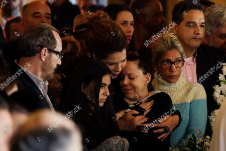 Stock Photo of Bebel Gilberto, daughter of late Brazilian cultural icon Joao Gilberto, center right, is comforted during her father's wake at the Municipal Theater in Rio de Janeiro, Brazil, . Joao Gilberto, one of the fathers of bossa nova music who gained worldwide popularity in the 1960s, passed away in his home in Rio de Janeiro on Saturday. He was 88