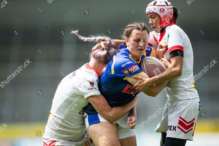Shannon Lacey of Leeds is tackled by Naomi Williams and Zoe Harris of St Helens.