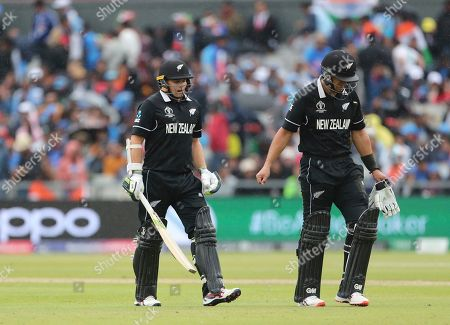 New Zealand's Ross Taylor, right, and Tom Latham leave the field after rain stopped play during the Cricket World Cup semi-final match between India and New Zealand at Old Trafford in Manchester, England