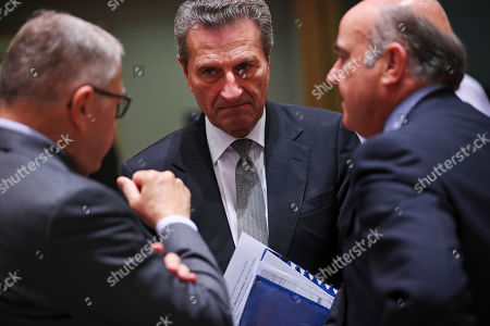 Stock Image of Gunther Oettinger, Luis de Guindos, Klaus Regling. European Commissioner for Budget and Human Resources Gunther Oettinger, center, talks to Klaus Regling, left, Managing Director of EMS (European Stability Mechanism) and European Central Bank Vice President Luis de Guindos during the European Finance Ministers meeting at the European Council headquarters in Brussels