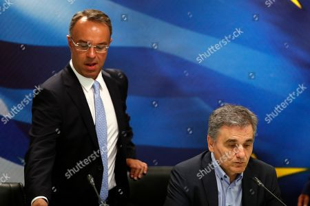 New Finance Minister Christos Staikouras, left, arrives as outgoing Finance Minister Euclid Tsakalotos takes a seat during a handover ceremony in Athens, . Greece's new Cabinet was sworn in Tuesday, two days after conservative party leader Kyriakos Mitsotakis won early elections on pledges to make the country more business-friendly, cut taxes and negotiate an easing of draconian budget conditions agreed as part of the country's rescue program