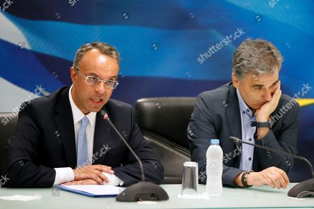 New Finance Minister Christos Staikouras, left, speaks as outgoing Finance Minister Euclid Tsakalotos is seen during a handover ceremony in Athens, . Greece's new Cabinet was sworn in Tuesday, two days after conservative party leader Kyriakos Mitsotakis won early elections on pledges to make the country more business-friendly, cut taxes and negotiate an easing of draconian budget conditions agreed as part of the country's rescue program
