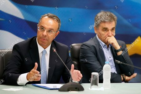 Stock Photo of New Finance Minister Christos Staikouras, left, speaks as outgoing Finance Minister Euclid Tsakalotos is seen during a handover ceremony in Athens, . Greece's new Cabinet was sworn in Tuesday, two days after conservative party leader Kyriakos Mitsotakis won early elections on pledges to make the country more business-friendly, cut taxes and negotiate an easing of draconian budget conditions agreed as part of the country's rescue program