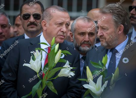 Turkey's president Rejep Tayyip Erdogan, left, and Bakir Izetbegovic, son of former Bosnia's president Alija Izetbegovic, hold flowers as they wait for the vehicle carrying the remains of 33 victims of the Srebrenica massacre, in Sarajevo, Bosnia, . The remains will be buried in Potocari near Srebrenica, on July 11, 2019, 24 years after Serb troops overran the eastern Bosnian Muslim enclave of Srebrenica and executed some 8,000 Muslim men and boys, which international courts have labeled as an act of genocide