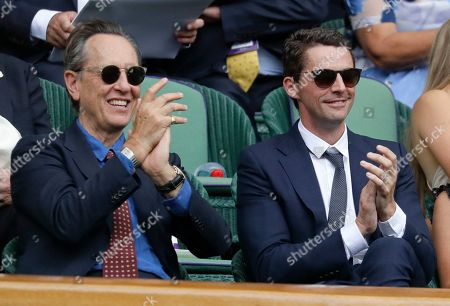 Actors Richard E. Grant, left, and Matthew Goode applaud while sitting in the Royal Box on Centre Court on day eight of the Wimbledon Tennis Championships in London