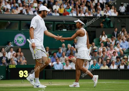Fabrice Martin of France and Raquel Atawo of the United States touch hands during a mixed doubles match on day eight of the Wimbledon Tennis Championships in London