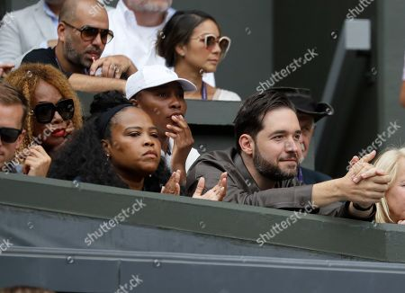 Alexis Ohanian, the husband of United States' Serena Williams, right, her sister Venus and her mother Oracene Price watch her play against United States' Alison Riske during a women's quarterfinal match on day eight of the Wimbledon Tennis Championships in London