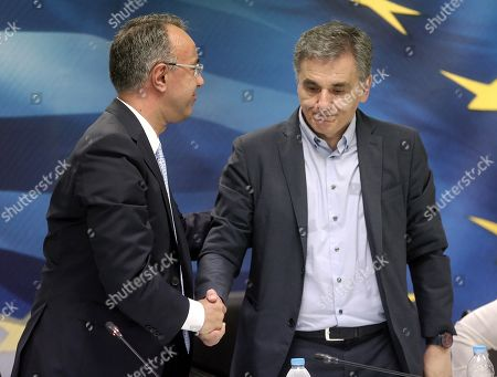 Newly appointed Finance Minister Christos Staikouras (L) shakes hands with the outgoing Finance Minister Euclid Tsakalotos (R) during a handover ceremony at the Finance Ministry in Athens, Greece, 09 July 2019. The center-right New Democracy party won the general elections in Greece on 07 July and formed a majority government.