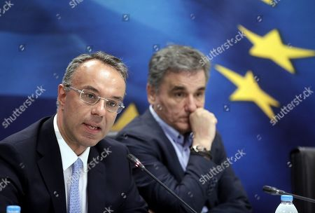 Stock Image of Newly appointed Greek Finance Minister Christos Staikouras (L) speaks next to outgoing Finance Minister Euclid Tsakalotos (R) during a handover ceremony at the Finance Ministry in Athens, Greece, 09 July 2019. The center-right New Democracy party won the general elections in Greece on 07 July and formed a majority government.