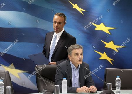 Newly appointed Greek Finance Minister Christos Staikouras (L) and outgoing Finance Minister Euclid Tsakalotos (R) arrive at the handover ceremony at the Finance Ministry in Athens, Greece, 09 July 2019. The center-right New Democracy party won the general elections in Greece on 07 July and formed a majority government.
