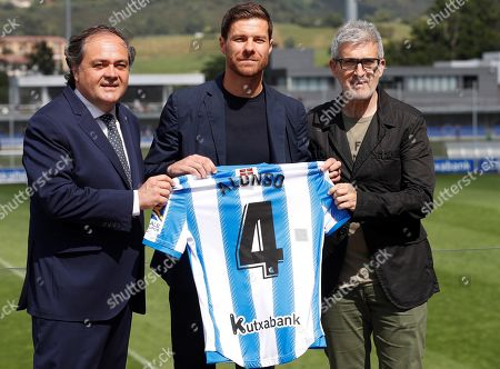 Spanish former player Xabi Alonso (C) poses for the media accompanied by Real Sociedad's president Jokin Aperribay (L) and Real Sociedad's sports director Robert Olabe (R) during his presentation as head coach of Sanse soccer team at Zubieta facilities, in Lasarte, Basque Country, Spain, 09 July 2019. Former Real Sociedad, Liverpool and Real Madrid midfielder Xabi Alonso has signed as the new head coach of Real Sociedad's B team (Sanse).