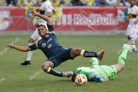 Club America midfielder Antonio Lopez (23), top, trips over Boca Juniors goalkeeper Marcos Diaz (12) during the first half of a Colossus Cup soccer match in Harrison, N.J