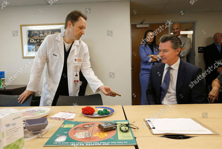 Gavin Newsom, Brian Shaw. Diabetes Program Coordinator Brian Shaw, left, shows Gov. Gavin Newsom various food items that diabetes patients should eat in moderation as Newsom stopped in the Diabetes Talking Circle at the Sacramento Native American Health Center in Sacramento, Calif., . Newsom visited the facility and discussed the earlier announcement that health insurance rates in California's individual market will increase an average of 0.8% in 2020, the lowest increase in five years