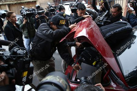 "Police put items, like a computer, into the trunk of a car during a search of the home of former President Ollanta Humala and wife Nadine Heredia in Lima, Peru, . Nadine Heredia is under investigation as part of the ""Lava Jato"" case, for allegedly receiving bribes from Odebrecht through the ""Gasoducto del Sur"" project, according prosecutors"