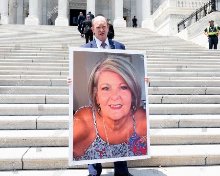 "U.S. Senator Christopher A. Coons (D-DE) holds up an images of a woman with pre-existing conditions on the steps of the U.S. Capitol during a rally against the ""assault on protections for people with pre-existing conditions"", in Washington, DC."