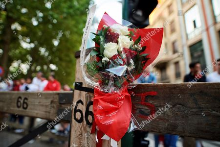 Close-up view of the flowers laid by late runner Daniel Jimeno Romero's parents (unseen) on the post number 66 of the Telefonica section of the Sanfermines track to pay a tribute to their son, died in this spot during a 'encierro,' or running-with-the-bulls, ten years ago, in Pamplona, Spain, 10 July 2019. The festival of San Fermin, locally known as Sanfermines, is held annually from 06 to 14 July in commemoration of the city's patron saint. Hundreds of thousands of visitors from all over the world attend the fiesta. Many of them physically participate in the highlight event - the running of the bulls, or encierro - where they attempt to outrun the bulls along a route through the narrow streets of Pamplona's old city.