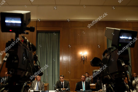 Greek Prime Kyriakos Mitsotakis (C)  surrounded by governmental Vice-President Panagiotis Pikrammenos (C-L) and finance minister Christos Staikouras (C-R) chairs the first cabinet meeting of the new government in the Parliament in Athens, Greece, 10 July 2019. Each minister will receive a file with a six-month plan of his area of responsibility, according to government sources. The dossier will detail the specific objectives to be achieved by each ministry by December and how to assess each governmental action.