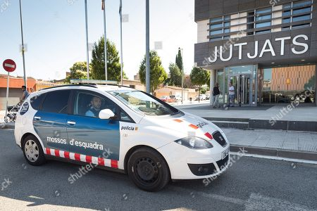 A couple of Mossos d'Esquadra officers stand guard inside a Catalan police's vehicle in front of the court in the town of La Bisbal d'Emporda, in Girona, northeastern Spain, 10 July 2019. A 18-years old childminder is to appear before the judge one day after he was arrested for allegedly committing sexual abuses of a 13-months old baby in the village of Palafrugell.