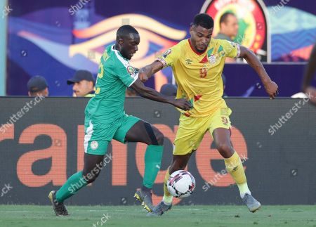 Stock Photo of Senegal's Youssouf Sabaly, left, and Benin's Steve Mounie fight for the ball during the African Cup of Nations quarterfinal soccer match between Senegal and Benin in 30 June stadium in Cairo, Egypt