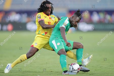 Benin's Sessi D'almeida, left, and Senegal's Lamine Gassama fight for the ball during the African Cup of Nations quarterfinal soccer match between Senegal and Benin in 30 June stadium in Cairo, Egypt
