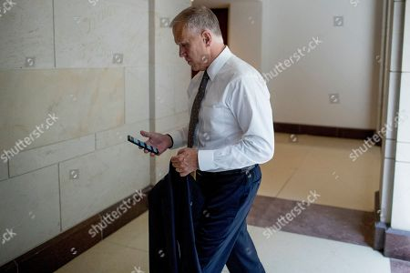 Amy Klobuchar. Sen. Thom Tillis, R-N.C., checks his phone as he arrives for a closed door meeting for Senators on election security on Capitol Hill in Washington