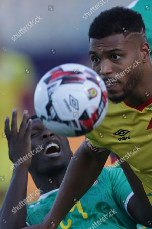 Benin's Steve Mounie, right, fights for the ball with Senegal's Lamine Gassama during the African Cup of Nations quarterfinal soccer match between Senegal and Benin in 30 June stadium in Cairo, Egypt