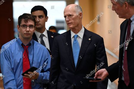 Sen. Rick Scott, R-Fla., center, talks with reporters on Capitol Hill in Washington, after attending a briefing on election security