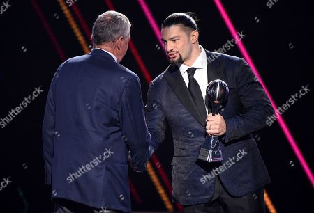 Stock Image of Roman Reigns, Jim Calhoun. Roman Reigns, right, presents the best coach award to Jim Calhoun, men's basketball coach for the University of Saint Joseph in West Hartford, Conn., at the ESPY Awards, at the Microsoft Theater