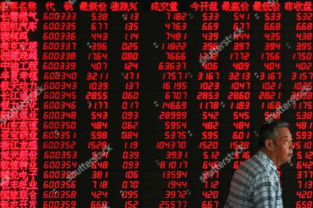 Stock Picture of An investor walks by an electronic board displaying stock prices at a brokerage house in Beijing, . Shares rose Thursday in Asia, tracking gains on Wall Street after Federal Reserve Chairman Jerome Powell suggested the U.S. central bank is ready to cut interest rates for the first time in a decade