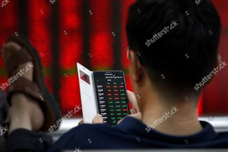 A man checks stock prices through his smartphone at a brokerage house in Beijing, . Shares rose Thursday in Asia, tracking gains on Wall Street after Federal Reserve Chairman Jerome Powell suggested the U.S. central bank is ready to cut interest rates for the first time in a decade